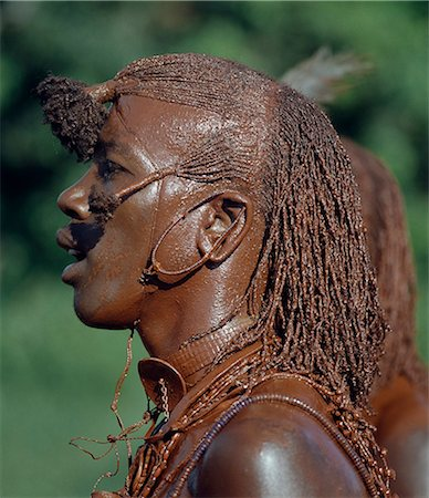 A Maasai warrior has daubed himself with red ochre mixed with animal fat to participate in a dance. His long ochred braids have been drawn forward from the crown of the head and tied in three places. This singular hairstyle sets warriors apart from the rest of their society. Stock Photo - Rights-Managed, Code: 862-03366151