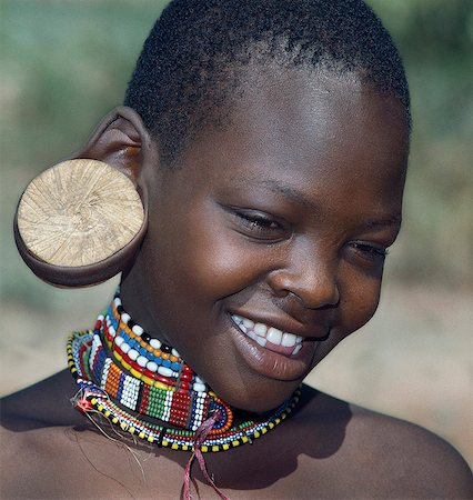 A young Maasai girl wearing a wooden plug in her pierced ear to elongate the earlobe. It has been a tradition of the Maasai for both men and women to pierce their ears and elongate their lobes for decorative purposes. Her two lower incisors have been removed - a common practice that may have resulted from an outbreak of lockjaw a long time ago. Stock Photo - Rights-Managed, Code: 862-03366174