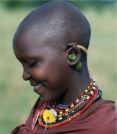 A young Maasai girl keeps the holes in her pierced ears from closing with grass and rolled leaves. She will gradually stretch her earlobes by inserting progressively larger wooden plugs. By tradition,both Maasai men and women pierce and elongate their earlobes for decorative purposes. Stock Photo - Rights-Managed, Code: 862-03366175