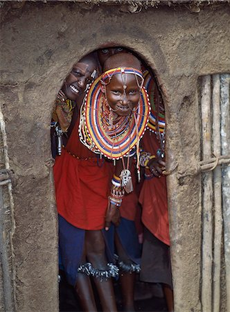 Maasai girls in all their finery and with bells tied round their legs wait at the entrance to a house before dancing with warriors. Stock Photo - Rights-Managed, Code: 862-03366171