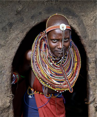 A young Maasai girl in all her finery pauses at the entrance to her mother's home. The wall and roof of the house are plastered with a mixture of cow dung and soil. Stock Photo - Rights-Managed, Code: 862-03366172