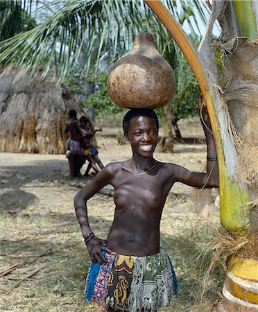 A Giriama girl from Kenya's Coast Province carrying a gourd full of water on her head. Her small skirt is made from strips of printed cotton material. Stock Photo - Rights-Managed, Code: 862-03366188