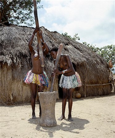 Two Giriama girls pound corn outside their home using a large wooden mortar and pestles. Their small skirts are made from strips of printed cotton material - a traditional dress of Giriama women and children. Stock Photo - Rights-Managed, Code: 862-03366189