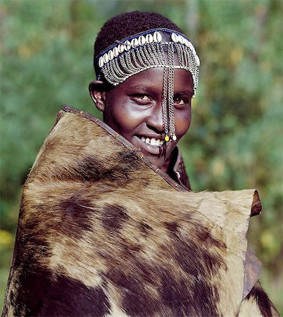 A girl from the Ogiek community of hunter-gathers living in the Mau Forest keeps warm in a cowhide. Following Maasai custom,she wears a decorated headband which marks her recent circumcision. Stock Photo - Rights-Managed, Code: 862-03366258