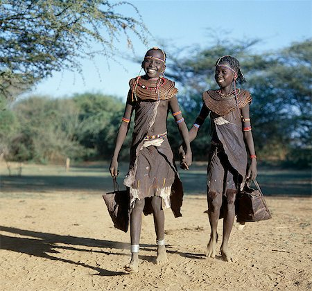 Two jovial Pokot girls set off with leather bags in search of edible berries. Pokot girls and women traditionally wore leather skirts and capes made from home-tanned goatskins. The necklaces of young girls are made from small segments of sedge grass. Stock Photo - Rights-Managed, Code: 862-03366279