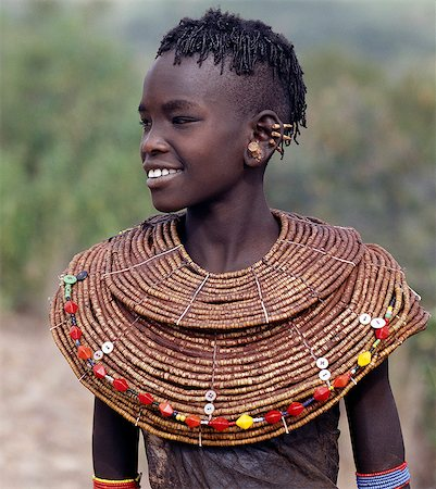 A young Pokot girl in traditional attire. Girls wear leather skirts and capes made from home-tanned goatskins. Her broad necklaces are made from small segments of sedge grass. Her ears have already been pierced in four places,ready to insert the large brass earrings she will acquire after marriage. Stock Photo - Rights-Managed, Code: 862-03366281