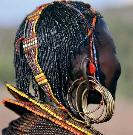 A close-up of a Pokot woman's earrings,hairstyle and beaded ornaments. Only married women wear brass earrings and glass-beaded collars. The band over her head supports the weight of her heavy earrings. Stock Photo - Rights-Managed, Code: 862-03366283