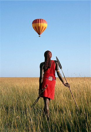 A Maasai Warrior watches a hot air balloon float over the Mara plains. Stock Photo - Rights-Managed, Code: 862-03366304