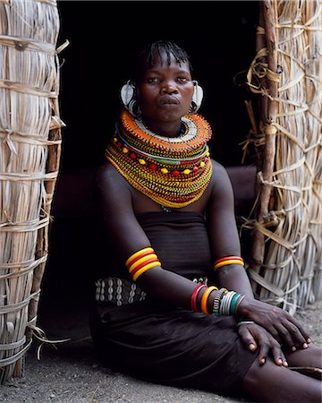 A Turkana woman,typically wearing many layers of bead necklaces and a series of hooped earrings with an pair of leaf-shaped earrrings at the front,sits in the entrance to her hut. Stock Photo - Rights-Managed, Code: 862-03366494
