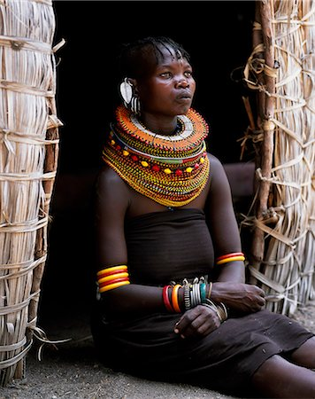 A Turkana woman,typically wearing many layers of bead necklaces and a series of hooped earrings with an pair of leaf-shaped earrrings at the front,sits in the entrance to her hut. Stock Photo - Rights-Managed, Code: 862-03366495