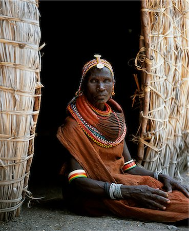 A Turkana woman sitting in the doorway of her hut. Her heavy mporro braided necklace identifies her as a married woman. Typical of her tribe,she wears many layers of bead necklaces and a beaded headband. Stock Photo - Rights-Managed, Code: 862-03366496