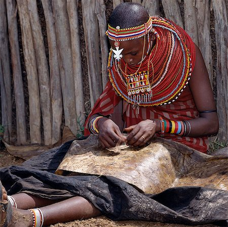 A Samburu woman sews a leather cloak for her younger brother. For several weeks before a boy is circumcised,he must wear a charcoal-blackened cloak,which is made from three goatskins. Stock Photo - Rights-Managed, Code: 862-03366539