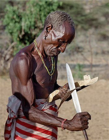 Kenya, Samburu District,  South Horr, Samburu District, Kenya. A ritual helper of a Samburu boy makes him new sandals the day before he is circumcised which he will wear for a month and then discard. Stock Photo - Rights-Managed, Code: 862-03366544