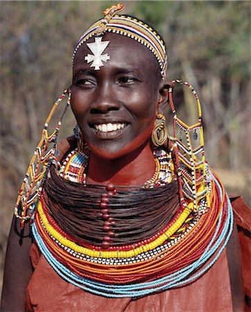 A Samburu woman wearing a mporro necklace,which signifies her married status.These necklaces,once made of hair from giraffe tails,are now made from fibres of doum palm fronds (Hyphaene coriacea). The beads are mid-19th century Venetian glass beads,which were introduced to Samburuland by early hunters and traders. Stock Photo - Rights-Managed, Code: 862-03366589