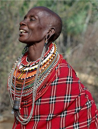 A Samburu woman singing. The strings of black and white beads hanging from her ears signify that she has two grown-up sons who are warriors of the tribe. Note: the traditional horn snuff container hanging from her neck. Stock Photo - Rights-Managed, Code: 862-03366590