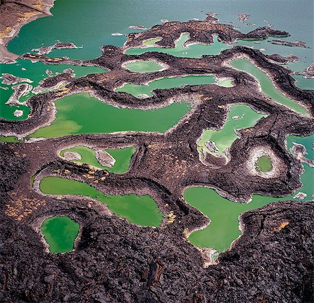 A series of lava rock pools are situated just off the southern end of Lake Turkana,northern Kenya's Jade Sea. The colour of the water is caused by extreme alkalinity in which green algae with a high chlorophyll content grows. Stock Photo - Rights-Managed, Code: 862-03366605