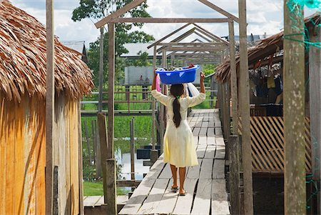 Peru,Amazon River. Indigenous Indian girl carrying her washing in the village of Islandia. Stock Photo - Rights-Managed, Code: 862-03360632