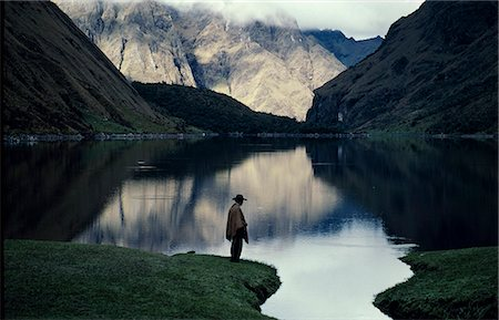 A high lake in the Vilcabamba range; at the waters edge a mule wrangler checks his fishing line at dawn. Stock Photo - Rights-Managed, Code: 862-03360705