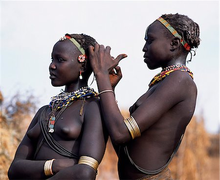 A Dassanech girl braids her sister's hair at her village in the Omo Delta. Much the largest of the tribes in the Omo Valley numbering around 50,000,the Dassanech (also known as the Galeb,Changila or Merille) and Nilotic pastoralists and agriculturalists. Stock Photo - Rights-Managed, Code: 862-03437084