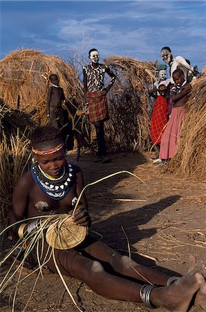 A Nyangatom girl weaves a grass basket. The Nyangatom or Bume are a Nilotic tribe of semi-nomadic pastoralists who live along the banks of the Omo River in south-western Ethiopia. Stock Photo - Rights-Managed, Code: 862-03437080