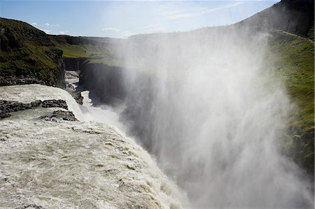 Iceland. Gullfoss (Golden Falls) is a magnificient 32m high double waterfall on the White River (Hvíta). The flow of the river from the regular rains and the glacial runoff,particularly in summer,makes it the largest volume falls in Europe. Stock Photo - Rights-Managed, Code: 862-03437101