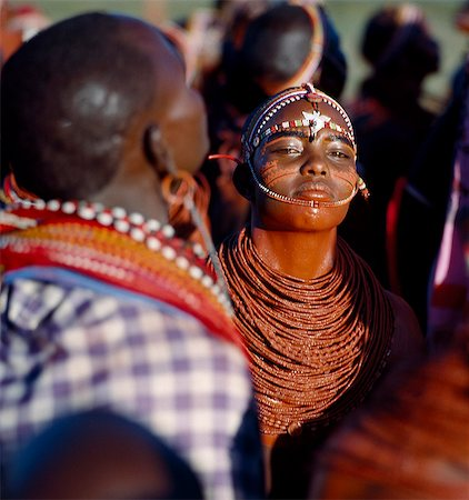 A young Samburu girl dances during a wedding celebration. By arching her back and thrusting out her chest,she flicks her beaded necklaces up and down while dancing silently to the songs of the warriors. Her body and necklace have been smeared with red ochre,and her eyebrows blackened with charcoal dust mixed with animal fat. Stock Photo - Rights-Managed, Code: 862-03437157