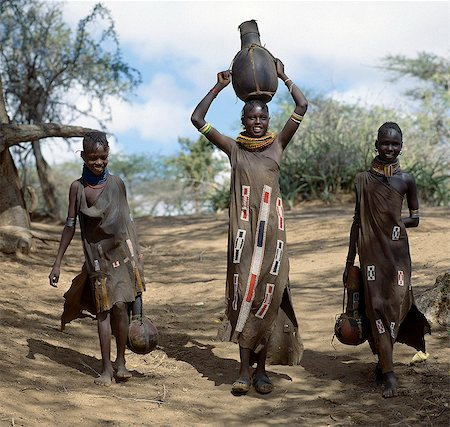 Turkana girls return home from a Waterhole with water containers made of wood. Their cloaks are goatskin embellished with glass beads. Stock Photo - Rights-Managed, Code: 862-03437159