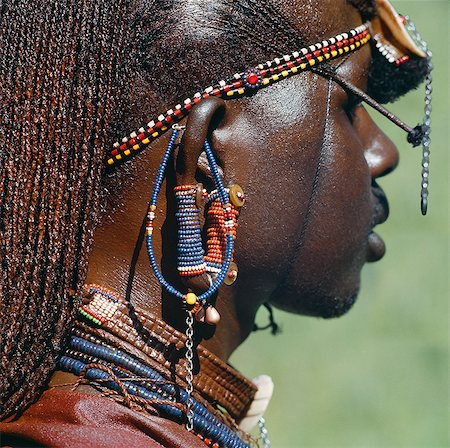 Detail of a Maasai warrior's ear ornaments and other beaded or metal adornments. The Maasai practice of piercing ears in adolescence and gradually elongating the lobes is gradually dying out. This warrior's body and his long braids have been smeared with red ochre mixed with animal fat. Stock Photo - Rights-Managed, Code: 862-03437160