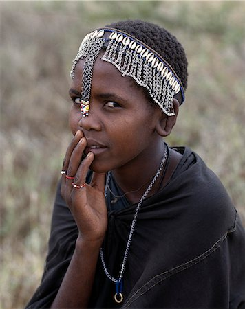 A young Maasai girl wears a headband decorated with chains and cowrie shells that signifies her recent circumcision. Clitodectomy was commonly practiced by the Maasai but it is now gradually dying out. Stock Photo - Rights-Managed, Code: 862-03437161