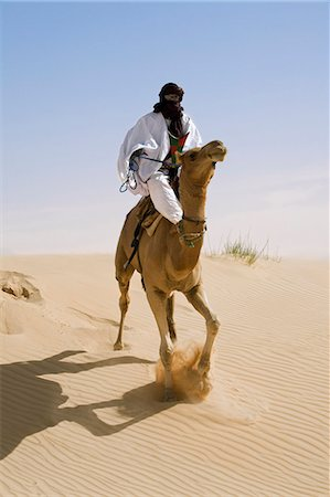 desert people dress photos - Mali,Timbuktu. In the desert north of Timbuktu,a Tuareg man rides his camel across a sand dune. He steers the animal with his feet. Stock Photo - Rights-Managed, Code: 862-03437232