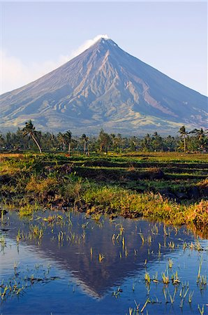 Philippines,Luzon Island,Bicol Province,Mount Mayon (2462m). Near perfect volcano cone with a plume of smoke and reflection in the water. Stock Photo - Rights-Managed, Code: 862-03437313