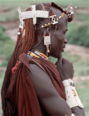 A warrior of the Kisongo section of the Maasai with his long Ochred braids decorated with beaded ornaments. His broad armulet is typical of the Kisongo living in northern Tanzania where white is the preferred colour of their beadwork. Stock Photo - Rights-Managed, Code: 862-03437401