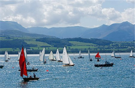 sports and sailing - Wales,Anglesey,Beaumaris. Dinghies race during a regatta on the Menai Straits against the backdrop of the Snowdonia Mountains. Stock Photo - Rights-Managed, Code: 862-03437762