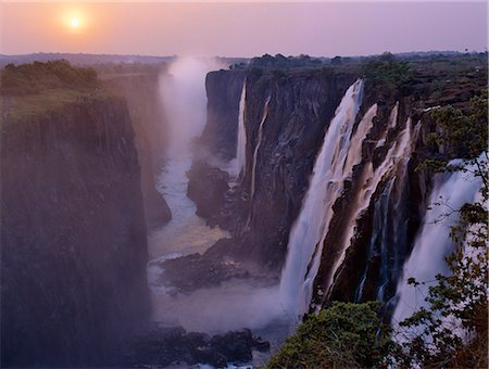 Sunset over the magnificent Victoria Falls. The Falls are more than a mile wide and are one of the world's greatest natural wonders. The mighty Zambezi River drops over 300 feet in a thunderous roar with clouds of spray. Stock Photo - Rights-Managed, Code: 862-03438059