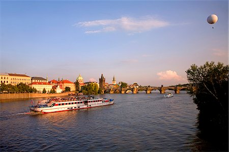 Czech Republic, Prague; A boat crossing the river Vltava and a cloudhopper viewing the city below. Stock Photo - Rights-Managed, Code: 862-03710839