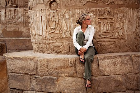 egyptian hieroglyphics - Egypt, Karnak. A tourist sits at the base of a massive stone column in the Great Hypostyle Hall. Stock Photo - Rights-Managed, Code: 862-03710911