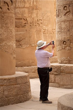 egyptian hieroglyphics - Egypt, Karnak. A tourist photographs the massive stone columns in the Great Hypostyle Hall. Stock Photo - Rights-Managed, Code: 862-03710913