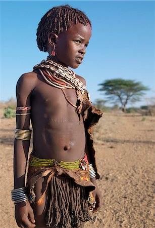 A Hamar girl in traditional attire. Her leather skirt is made from the twisted strands of goatskin. Cowries are always popular to embellish a woman's or girl's appearance.The Hamar are semi-nomadic pastoralists who live in harsh country around the Hamar Mountains of Southwest Ethiopia. Stock Photo - Rights-Managed, Code: 862-03711115
