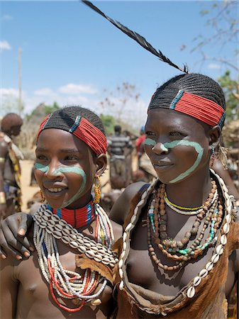 Two Hamar girl in fashionable dress at Turmi market. The Hamar are semi-nomadic pastoralists of Southwest Ethiopia whose women and girls wear striking traditional dress. Skins are widely used for clothing and heavy metal necklaces,bracelets and anklets form part of their adornments. Cowries are also popular yet the sea is 500 miles from Hamar country. Stock Photo - Rights-Managed, Code: 862-03711116