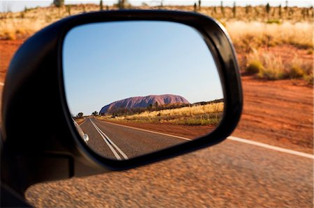 road landscape - Australia, Northern Territory, Uluru-Kata Tjuta National Park.  Uluru (Ayers Rock) in the rear vision mirror.   (PR) Stock Photo - Rights-Managed, Code: 862-03736290