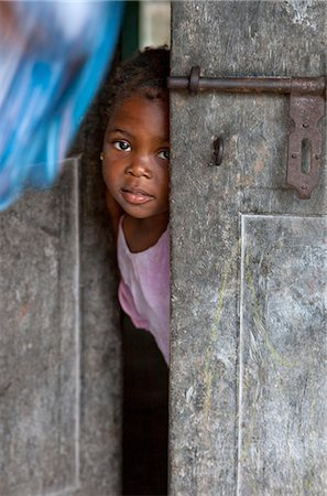 shy baby - Tanzania, Zanzibar. A young girl peeps out from the front door of her home at Nungwi, the northern tip of Zanzibar Island. Stock Photo - Rights-Managed, Code: 862-03737294