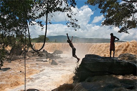 Kenya, A young man plunges into the foaming red waters of Fourteen Falls on the Athi River. Stock Photo - Rights-Managed, Code: 862-03731461