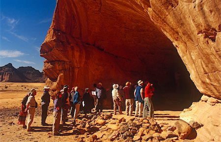 prehistoric - Libya, Fezzan, Jebel Akakus. Tourists gather at the mouth of Uan Amil, one of Wadi Teshuinat's caves. Stock Photo - Rights-Managed, Code: 862-03731756