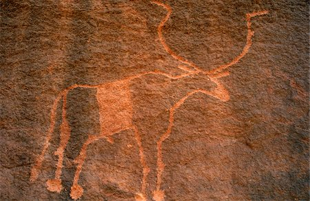 Libya, Fezzan, Messak Settafet. A petroglyph of a bovine with large sweeping horns, probably an African buffalo, Wadi Tiksatin Stock Photo - Rights-Managed, Code: 862-03731763