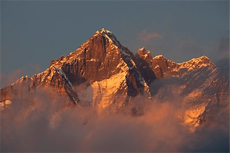 Nepal, Everest Region, Khumbu Valley. Shrouded in cloud on its lower slopes the peak of Mount Everest, known locally as Sagarmatha. Stock Photo - Rights-Managed, Code: 862-03731950