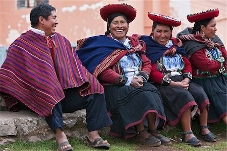 peru and culture - Peru, A man shares a joke with a group of native Indian women in traditional costume. Their saucer-shaped hats, beautifully decorated red jackets, black skirts and hand-woven woollen blankets round their shoulders are typical of the region. Stock Photo - Rights-Managed, Code: 862-03732055