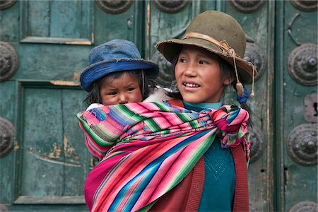 peru and culture - Peru, A young Peruvian girl carries her baby sister on her back beside the massive church doors of Iglesia de la Compania de Jesus in Cusco s Plaza de Armas. Stock Photo - Rights-Managed, Code: 862-03732083