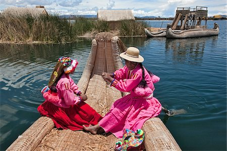 peru and culture - Peru, Two girl from Uros row a reed boat to one of the unique floating islands of Lake Titicaca. Stock Photo - Rights-Managed, Code: 862-03732107