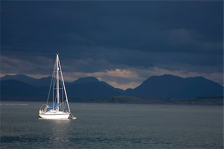 sailing boat storm - Scotland, Isle of Mull. Sunlit yacht in the Sound of Mull against a dramtic stormy sky. Stock Photo - Rights-Managed, Code: 862-03732288