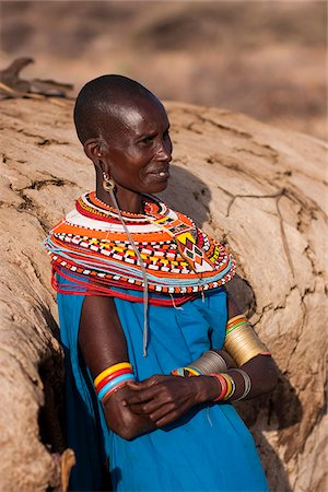 Kenya, Samburu District.  A Samburu woman, wearing intricate beaded necklaces, leans against her mud hut towards the end of the day. Stock Photo - Rights-Managed, Code: 862-03807765